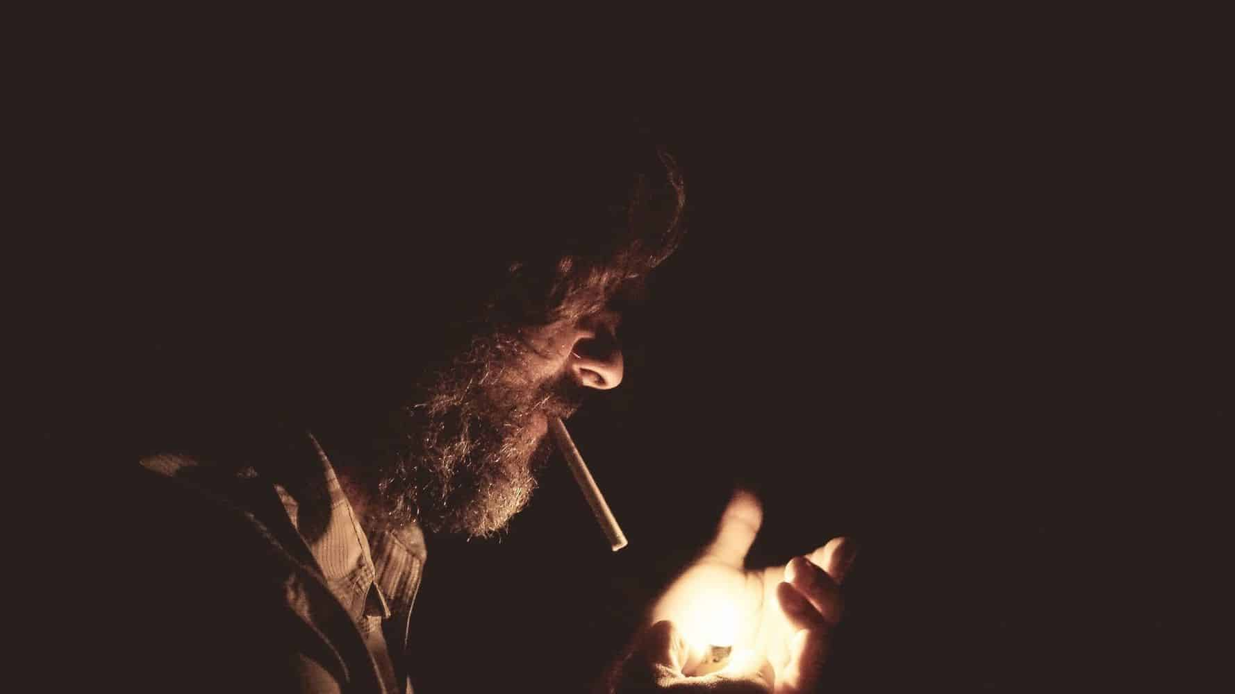 A person lighting a cigarette in the dark.