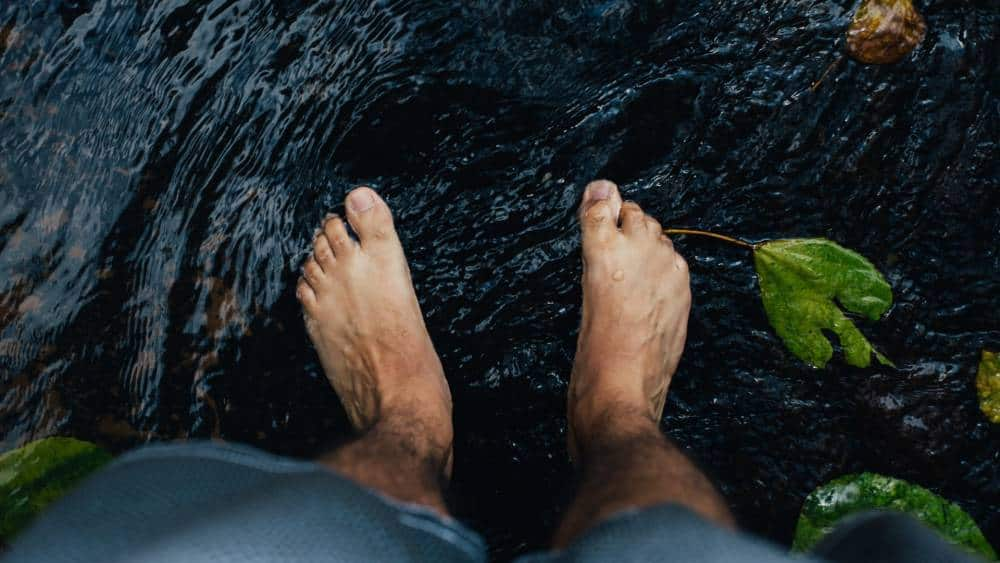 A man's feet in water.