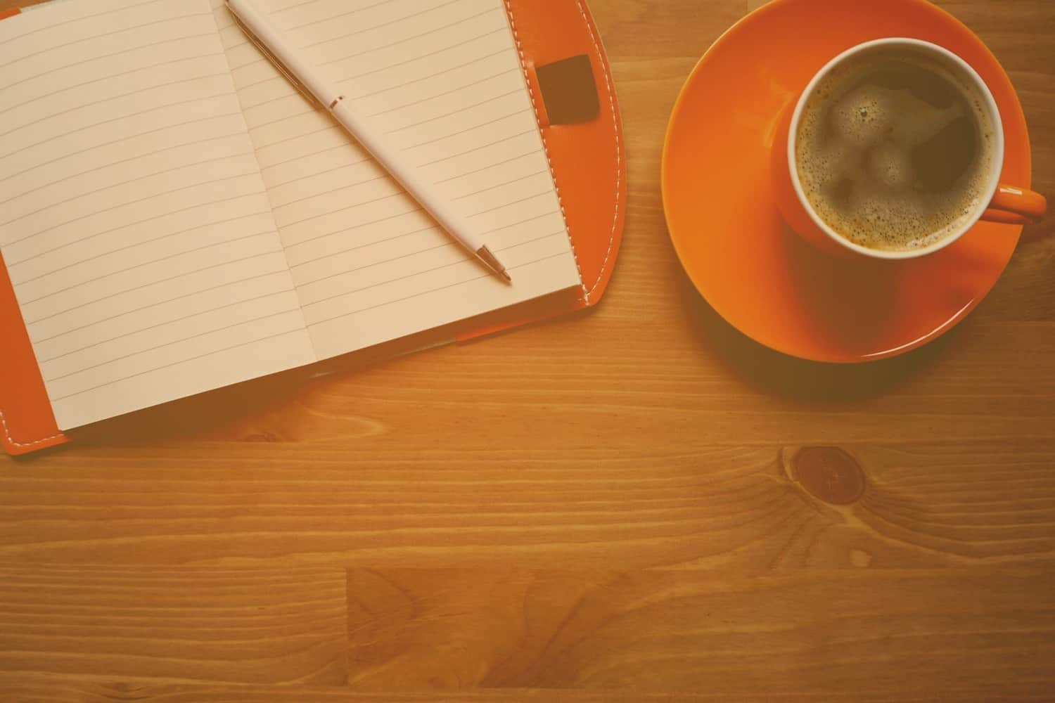 A cup of coffee with a notebook.