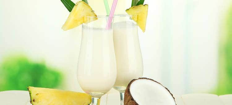 Two glasses of pineapple-coconut shake next to a coconut shell and a slice of pineapple, with pineapples on the glasses.