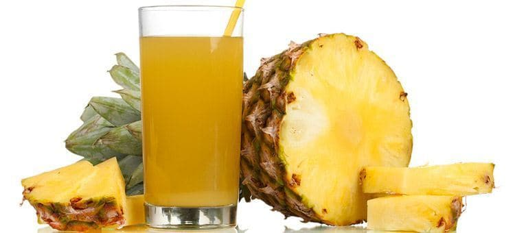 A glass of pineapple juice next to half of a pineapple.