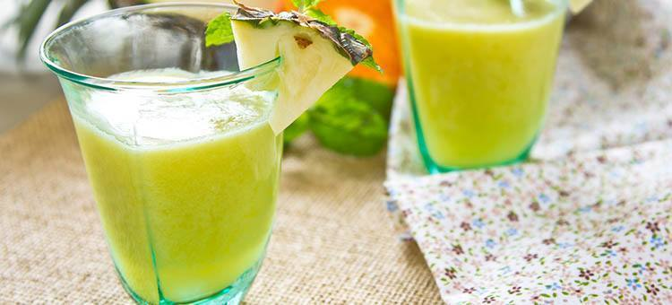 Glasses of greenish pineapple smoothie.