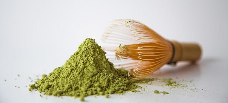 Powdered green matcha next to a flower.