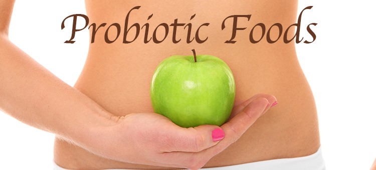 "A woman holding an apple in front of her belly with the title ""Probiotic Foods."""