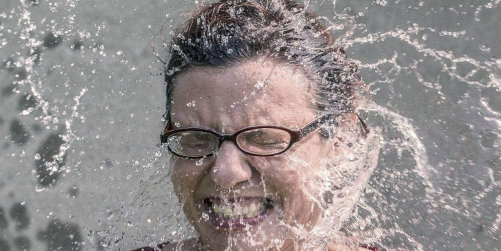 A woman being splashed with in the face with water.
