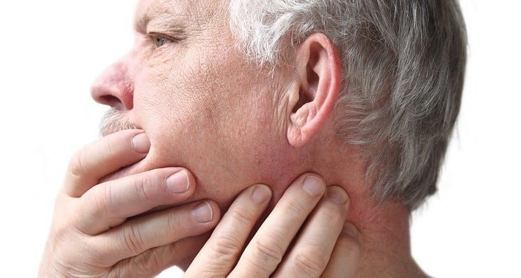 A person touching his jaw and examining his tmj.