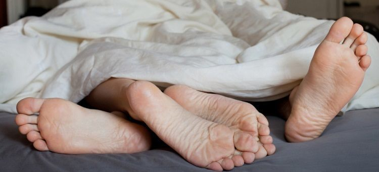 Feet of a couple in bed probably having sex.