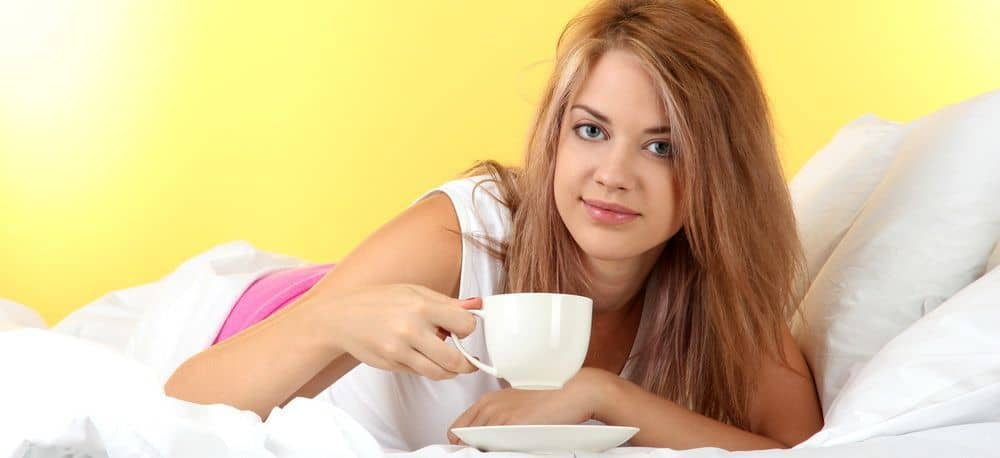 A woman with slightly messy hair drinking coffee in her bed.