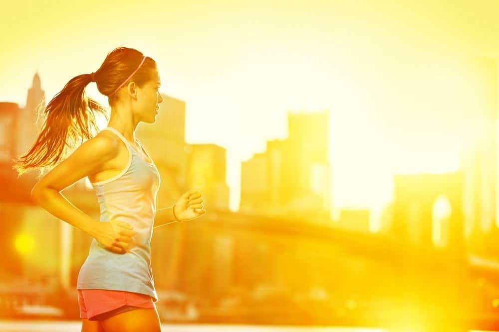 A woman running during sunset with a city in the background.