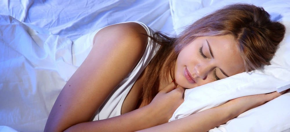 A young woman sleeping in her bed with a tranquil expression on her face.