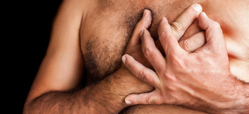 A man with a hairy chest holding is hands to his heart.