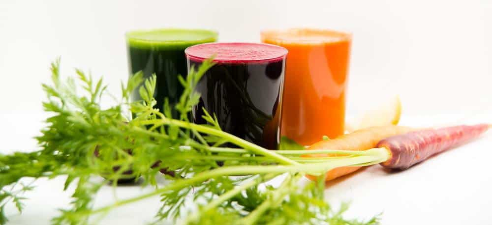 Three glasses of vegetable juice surrounded by carrots.