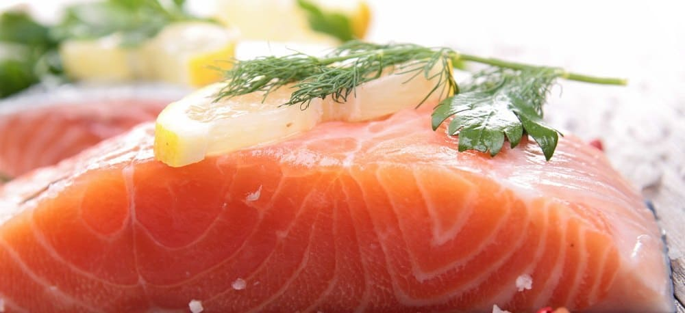 A large slice of salmon with a sice of lemon and some green spice for decoration.