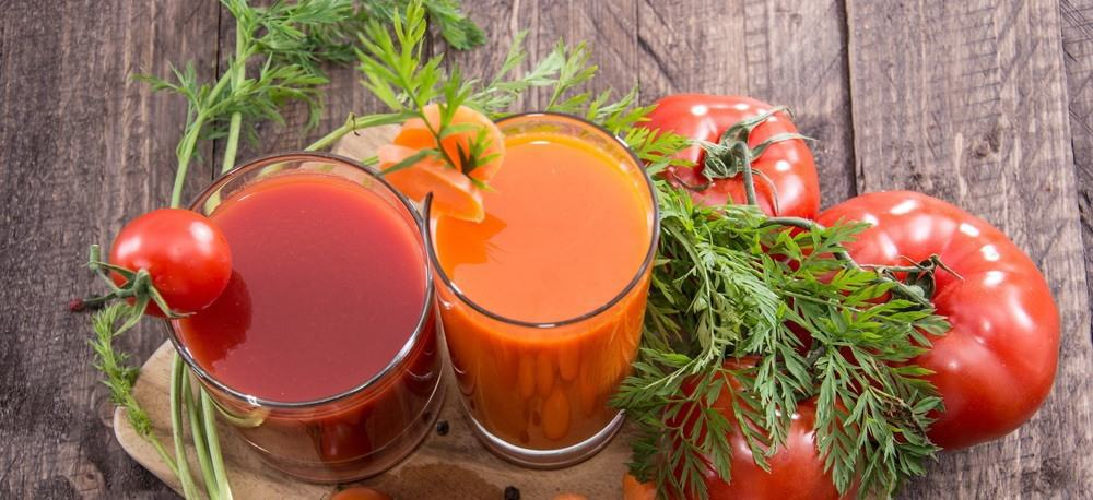 Two glasse sof vegetable juice next to tomatoes and carrots.