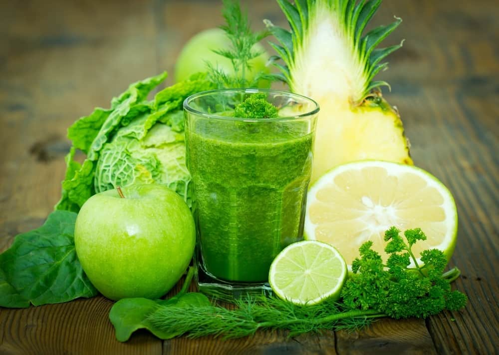 A glass of green juice next to apples, limes, pineapple and cabbage.