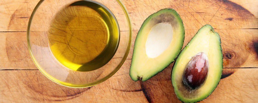 A glass of avocado oil and an avocado sliced in two.