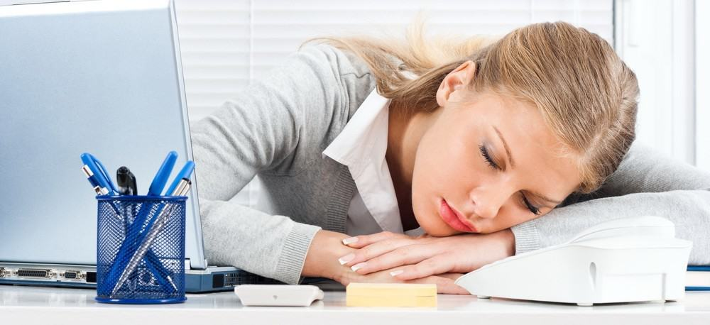 A businesswoman taking a nap at her desk.