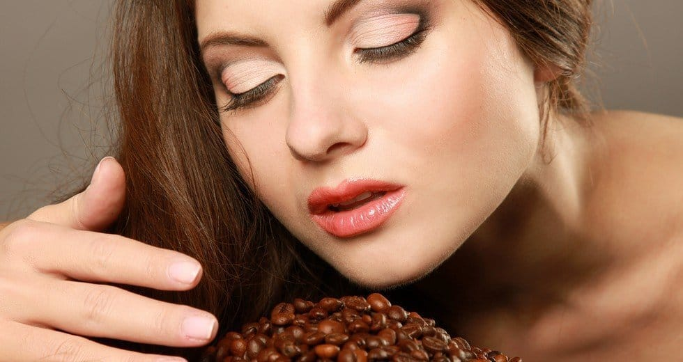 A woman taking deep breaths above a pile of coffee beans.