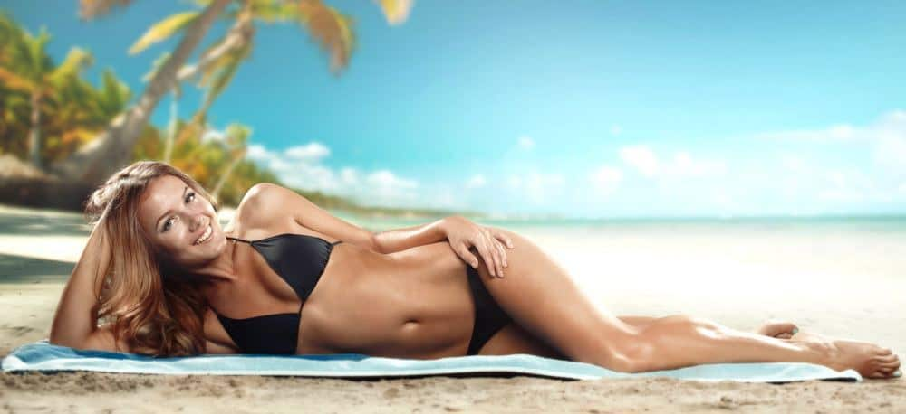 An oiled up fit woman in a bikini, posing on a beach shore.