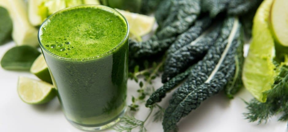 A glass of kale juice next to a batch of kale.