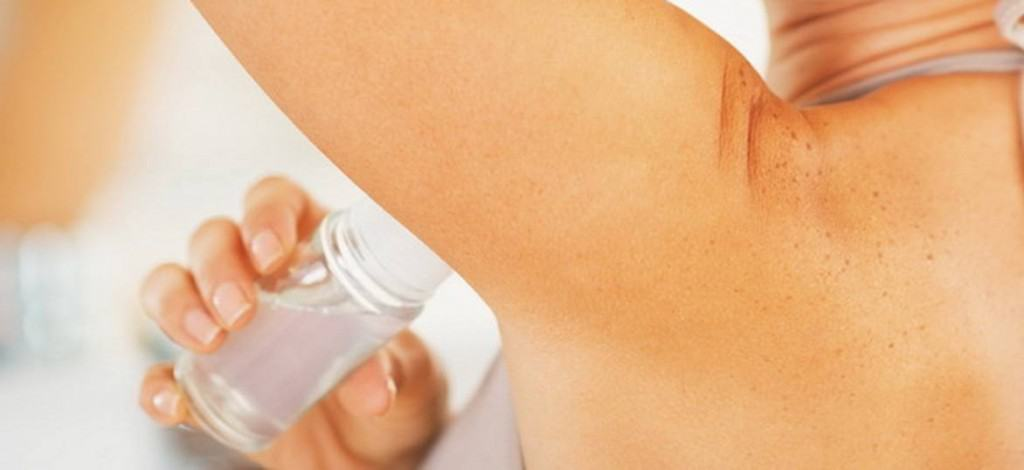 A woman applying deodorant to her armpits.
