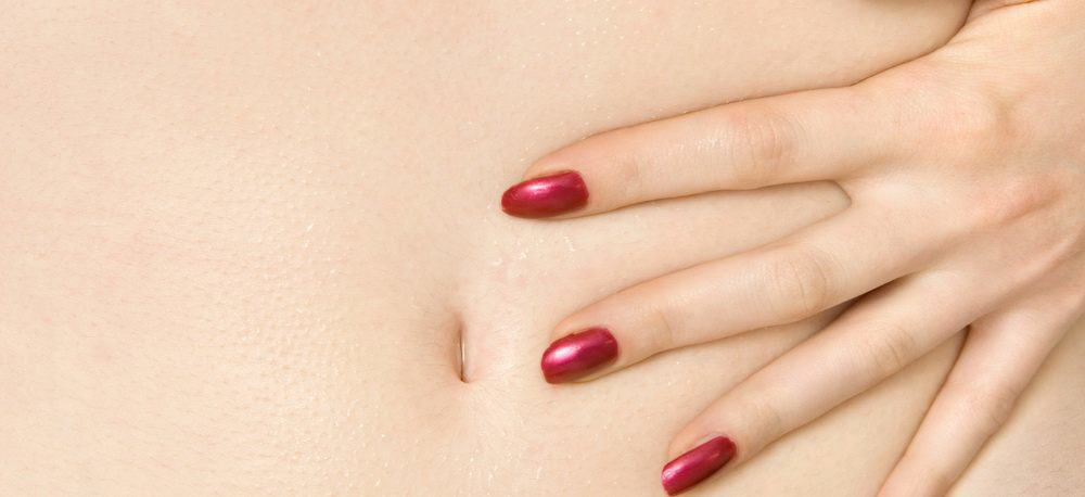 close-up of a woman holding her stomach with her hand as if in pain or discomfort.