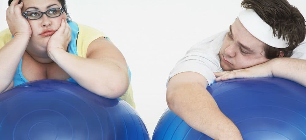 An overweight man and woman leaning on their fitness balls while looknig exhausted and demotivated.