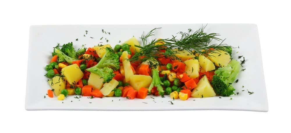 A plate of cooked vegetables including potatoes, carrots, broccoli, etc.