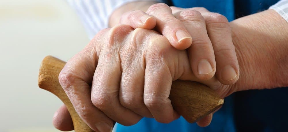Close-up of hands of an elderly man leaning on his wooden cane.