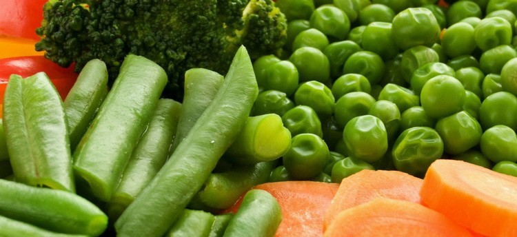 Close-up of various vegetables like peas and carrots.