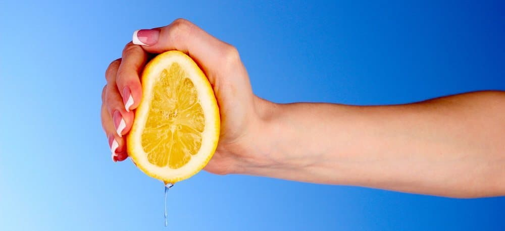 Hand of a woman squeezing a lemon.
