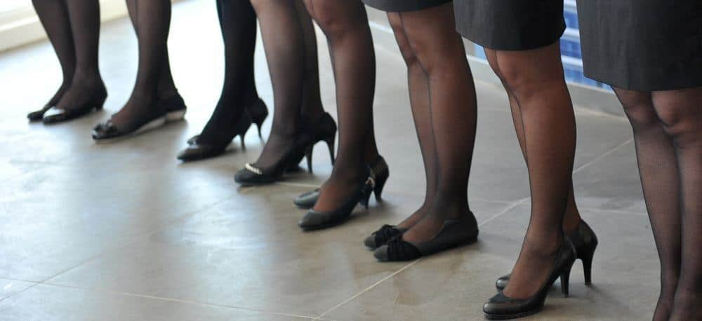 Image of legs of several women in office attire.