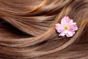 Shiny brown wavy hair with a small flower.