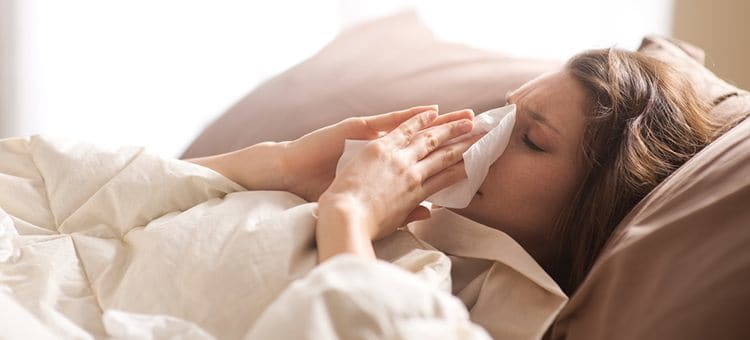 A woman cleaning her nose with a tissue in her bed.