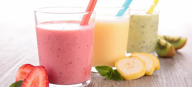 Glasses of various smoothies with slices of strawberry, kiwi, and maca next to them.