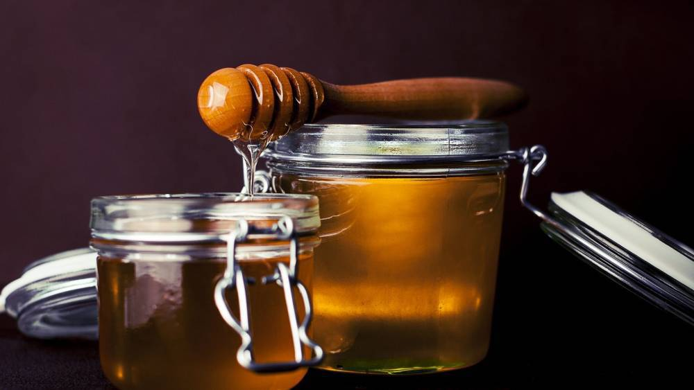 A jar of honey with a spoon.