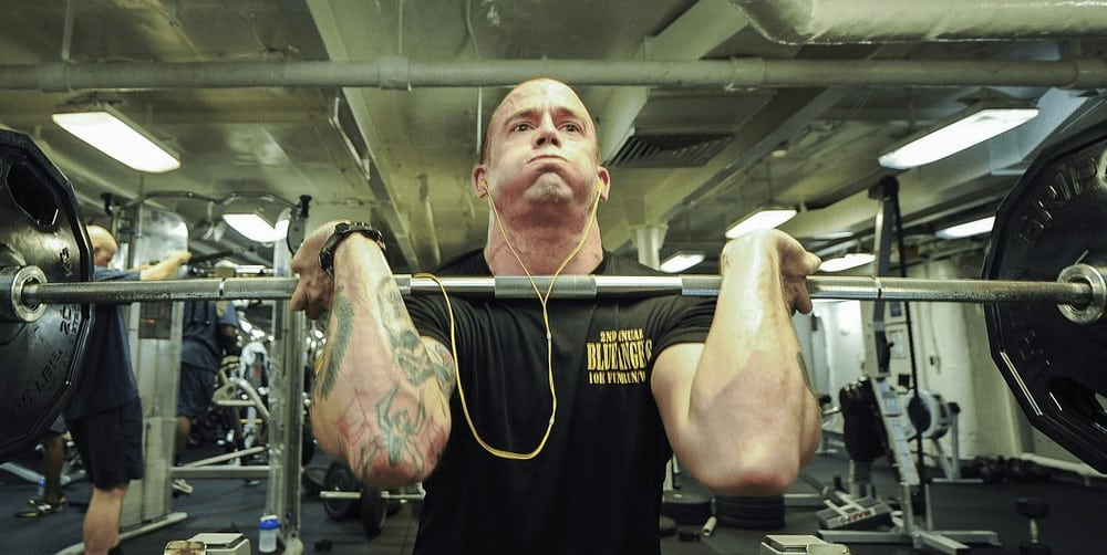 A man performing a squat with weights in a gym.