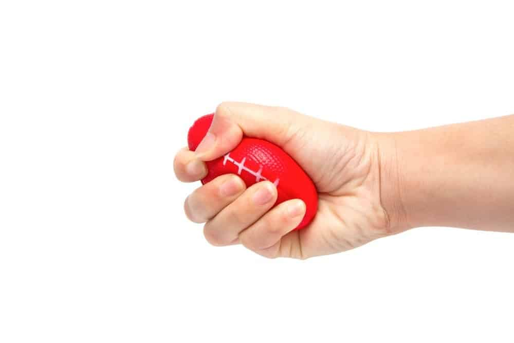 A hand squeezing a squeeze ball.