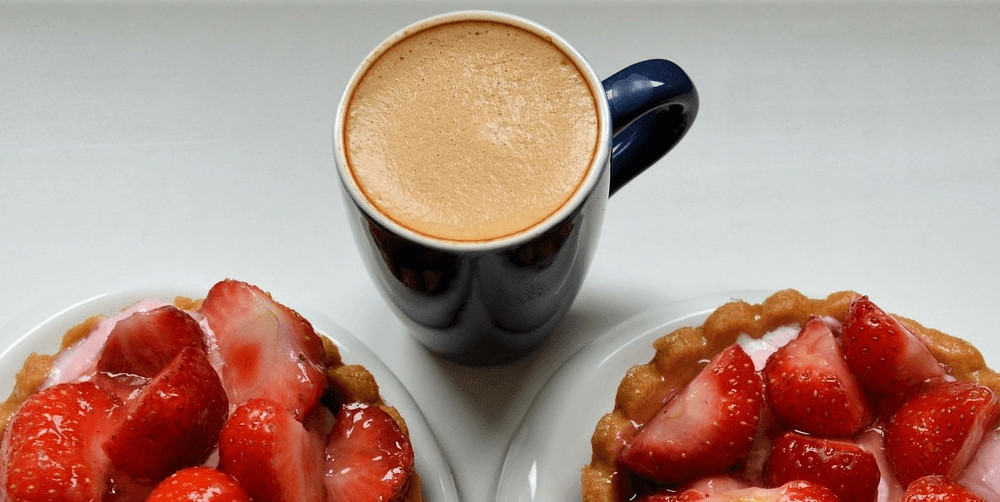 A mug of strawberry coffee with plates of strawberries.