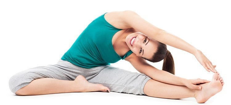 A woman smiling during a stretching exercise.