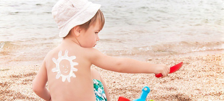 A young child with sunscreen on it's back in the form of a sun.
