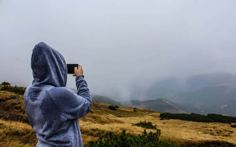 A person taking a photo during a hike.