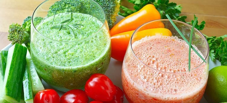 Red and green vegetable smoothies surrounded by carrots, cucumbers and tomatoes.