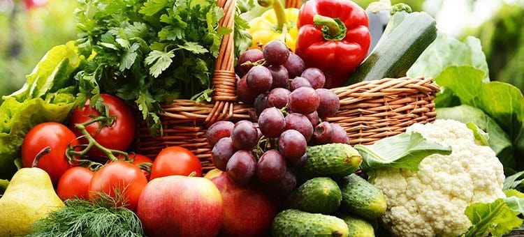 A basket of vegetables and fruit like peppers, grapes, cucumbers, tomatoes, etc.