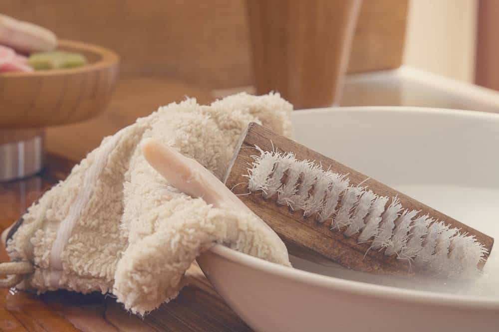 Washcloth with a brush in a bowl.