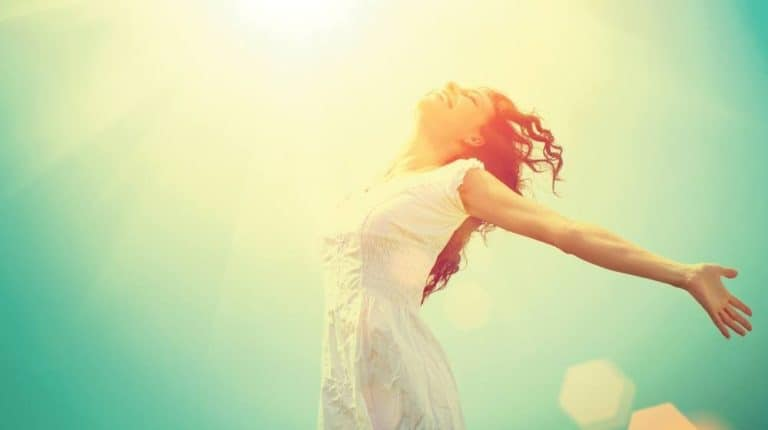 A woman gleefully enjoying the sun light with arms wide open.