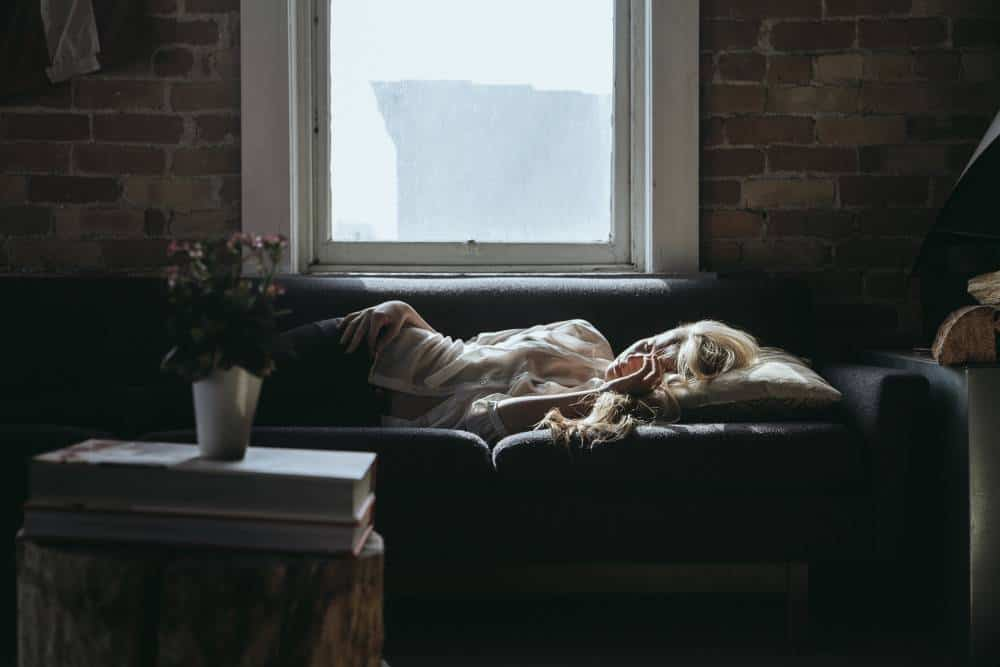 A woman sleeping on a couch.