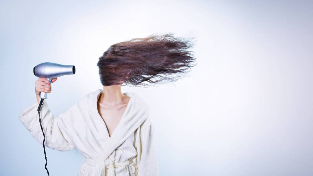 A woman blow-drying her hair.