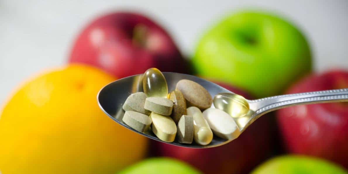 A spoonful of vitamin capsules in front of a background of fruit.