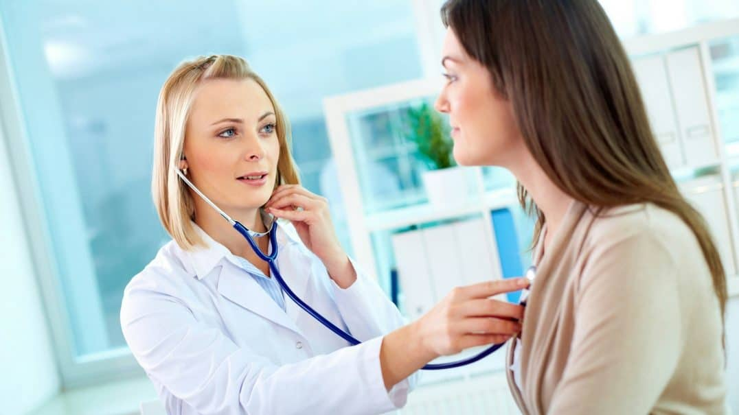 A doctor examining a patient with a stethoscope.